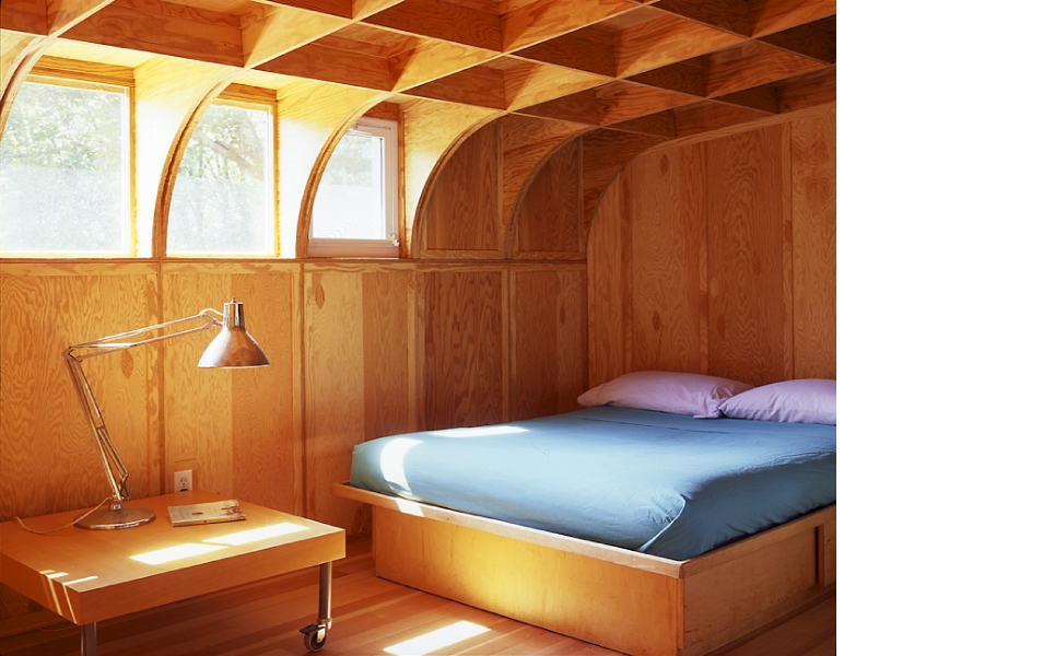 In a space overwhelmed by warm wood tones, cool-colored bedding can lend a modern feel. Source