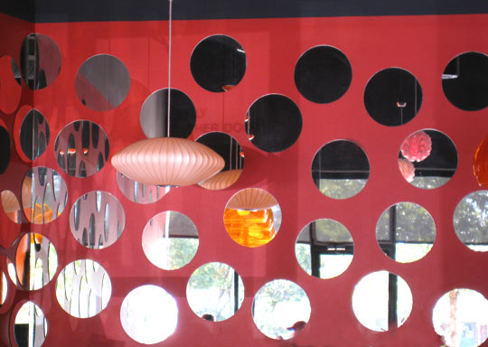 For a contemporary effect, the Galaxy Cafe in Austin created an arrangement of circular mirrors on a bold red wall. Source