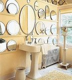 A vast collection of antique mirrors sitting on shelves makes a very plain bathroom a memorable one. Source
