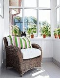 A simple pink stripe in this green pillow adds a minimal yet effective feminization of this sun porch. Source