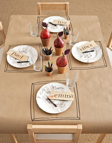 For a kids' table, keep activities, such as crayons and butcher paper tablecloths, nearby. I love the drawn placemats! Source