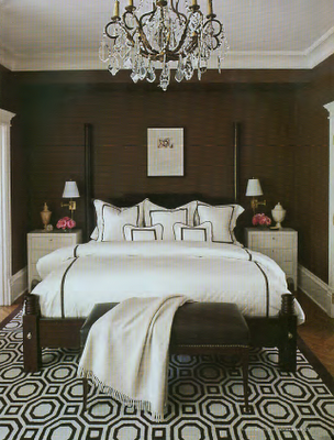 Chocolaty brown walls provide a pretty contrast to the crisp white bedding in this boudoir. Overall, the space is cozy and warm. Source