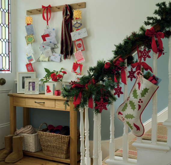 Bright red ribbons and red snowflakes add color and cheer to this banister garland. Source