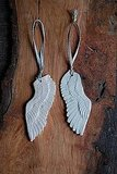 These Angel Wing Ornaments ($24) are earthenware ceramic pieces that have been glazed with a glossy clear glaze and dangle from metallic ribbons.