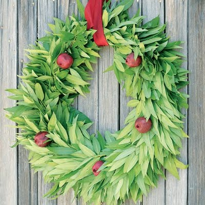 Pomegranates add a touch of color to a bay leaf wreath. You can get a plain wreath and augment it with fruit for a similar look. Source