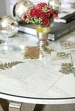 Slip holiday cards under a glass tabletop.  Source