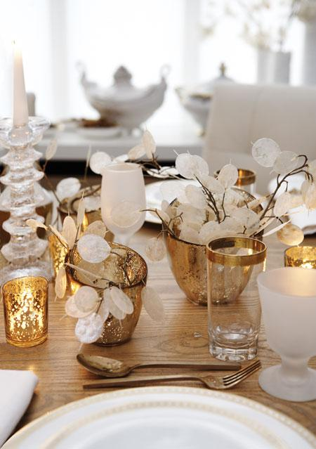 Frosted glasses and gold tableware create a sophisticated and glamorous holiday table setting. Source
