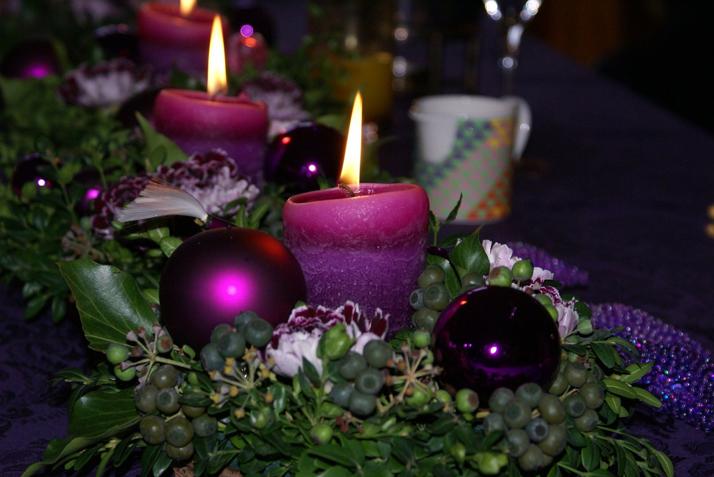 Greenery, candlelight, and Christmas ball ornaments are a foolproof centerpiece. Spice it up by using alternative colors. Source: Flickr User Laenulfean