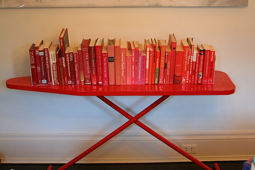 Create an eye-catching, easily movable bookshelf by using an unusual table or other furniture piece, such as a powder coated ironing board. Source:  Flickr User ninahale