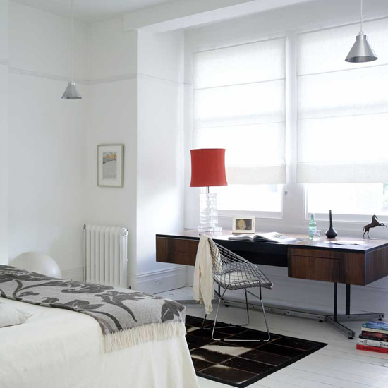 Create a work space in your bedroom by sliding a slim desk into a corner or window alcove. Source
