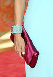 Lara Spencer's bright turquoise cuff and cranberry satin clutch.