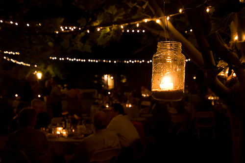 The bride and groom behind the blog A Backyard Wedding provided lighting for their backyard reception by hanging mason jars with candles in them. I love the effect. Source