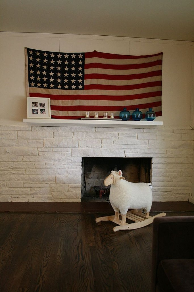 I love the understated look of this living room, where the flag takes center stage. Did you notice the two missing stars on this flag? It's because it's an antique!  Source