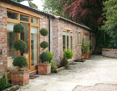 This charming brick barn home is dressed up with manicured topiary.  Source