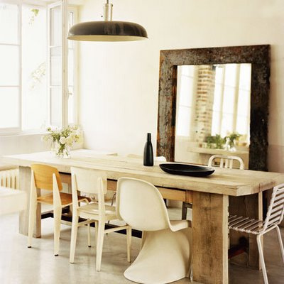An oversize mirror reflects great conversation and dinner party fun at this eclectically mixed dining room arrangement. Chairs in white, including a Verner Panton Chair ($1,405) contrast nicely with this rough-hewn farm table. Source
