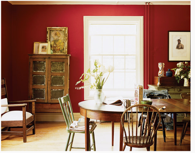 A brick red wall color and classically shaped wooden chairs give this room an all-American look.  Source