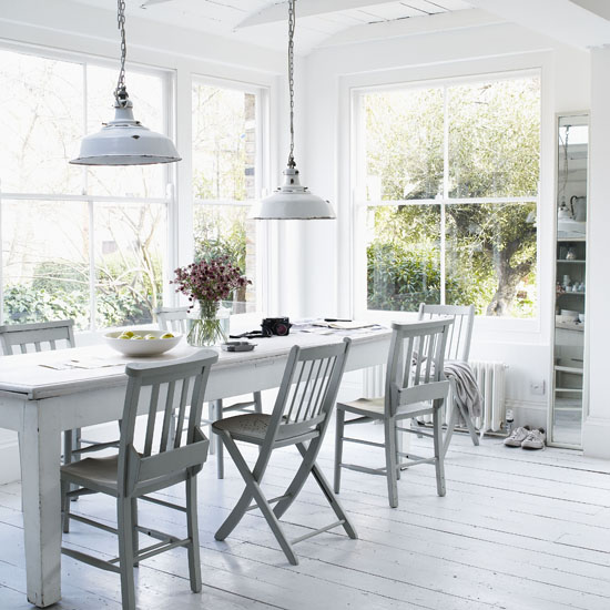 I love the cool white and gray tones in this sunny dining room. The industrial pendants above the table, with their worn patina, work perfectly in the space. And even though the chairs are mismatched, the paint job unifies the look. If you're shy about experimenting with mismatched dining chairs, try painting them the same color.  Source