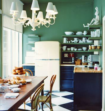 Drew Barrymore's collection of white dishes in her production company office kitchen pops thanks to its placement on green open shelves painted to match the walls.   Source