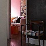A soft pink wall is given added strength thanks to the orange coffee table and variety of throw pillows. Source