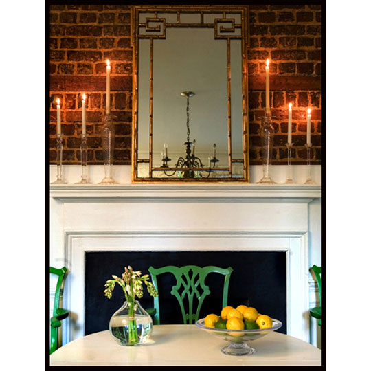 Since Fall isn't nearly as chilly in the South, candles can add ambiance and warmth when a lit fire would simply be too hot. By using tall glass candle holders on the mantel, the candlelight adds a warm glow to the brick wall in this room, and the green chairs add a pop of color.  Source