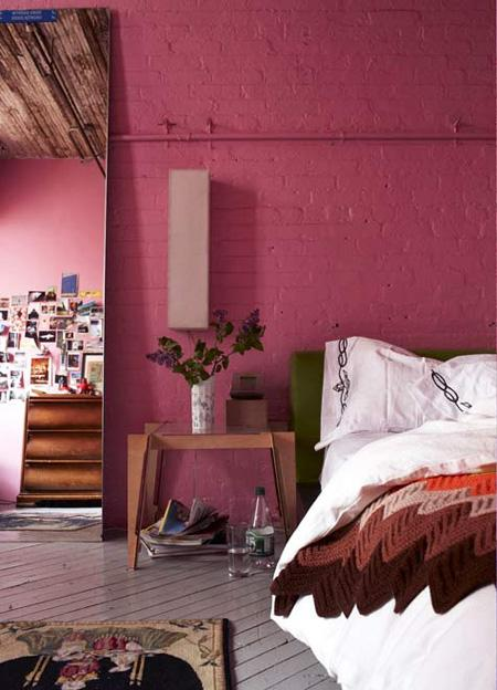 The saturated raspberry tone of this wall is offset by the more utilitarian look of the crocheted afghan, which has an orange zigzag stripe.  Source