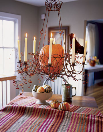 Create an unexpected candle chandelier with a pumpkin centerpiece that floats above the table. Fun!  Source