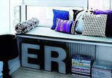 Utilize the space under a low bench by stacking magazines. Don't stop there, though: make the space eye-catching by also displaying more decorative objects, like these oversize letters. Source