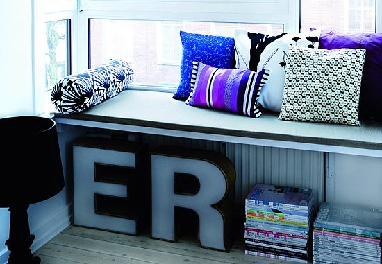 Utilize the space under a low bench by stacking magazines. Don't stop there, though: make the space eye-catching by also displaying more decorative objects, like these oversize letters.