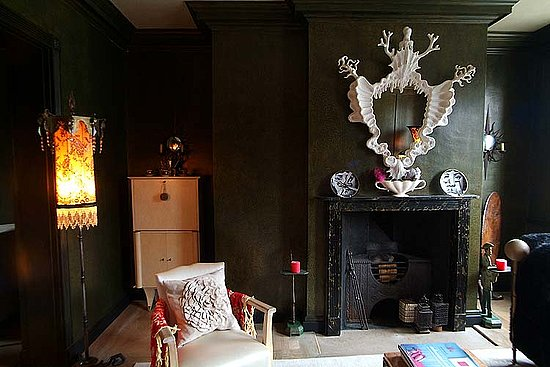 These olive-green walls are murky and moody, and the skeletal-like mantel decoration gives the room a spooky vibe.  Source