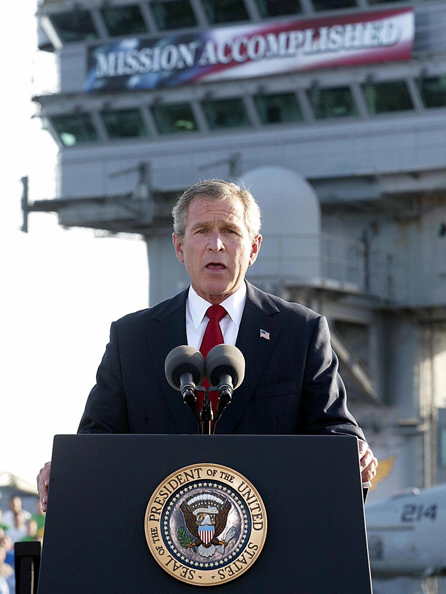 "Bush speaks beneath a banner reading ""Mission Accomplished"" on the USS Abraham Lincoln, May 1, 2003."