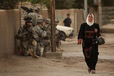A woman walks past a group of US soldiers in the war ravaged Hadar neighborhood March 10, 2008 in Baghdad.