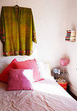 This image is from Maria's Oh So You Bungalow, a house tour on Apartment Therapy. Here, an embroidered, green tunic takes the place of a headboard in a primarily pink bedroom, tempering the room with its color and giving the eye a place to focus. Source