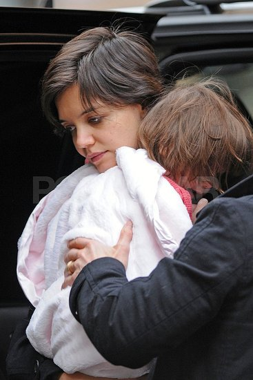 Tom and Katie Carry a Bundled up Suri