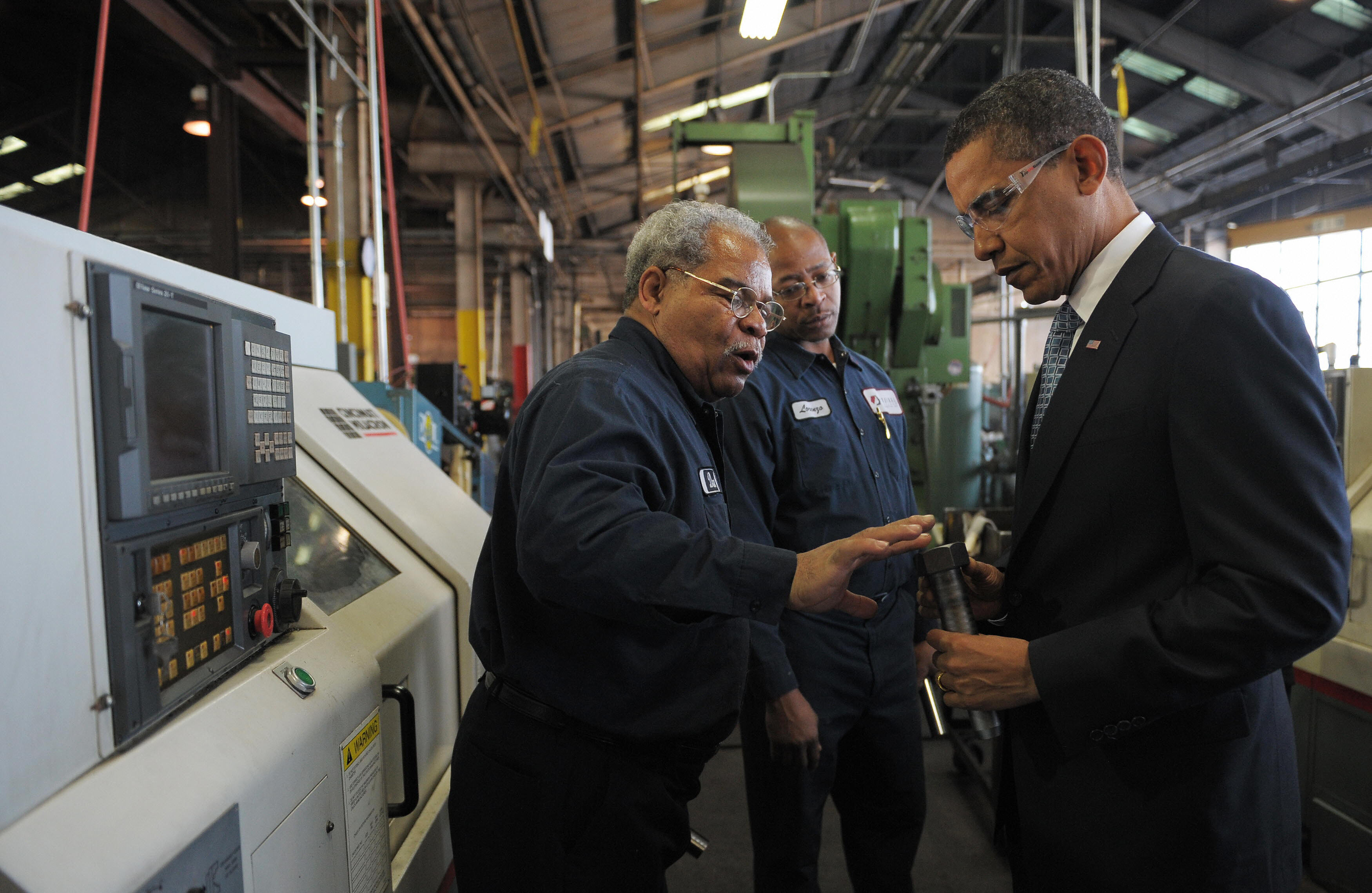 Barack Obama picks up a bolt during a tour of the Cardinal Fastener & Specialty Company factory.