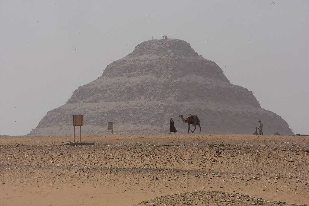 "A man walks with his camel on a foggy day past the Step Pyramid of Sakkara, located in the same region as the ""Headless Pyramid."