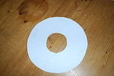 Next, cut a large circle out of a sheet of poster board or construction paper.  Cut a smaller hole out of the center.