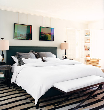 Walls, bedding, furniture, and lampshades in varying tones of white and cream create a soothing palette, which is in contrast to the busy stripes on the floor.