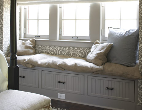A window seat does double duty as a storage space.