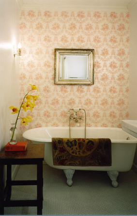 An antique-inspired wallpaper pattern pairs well with the Victorian clawfoot tub.