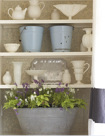 A galvanized steel tub, filled with flowers, is a rustic touch to the clean lines of porcelain and pottery.