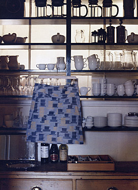 A cup-covered apron hangs alongside cheery white cups and plunge pots.