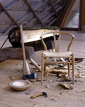 A Hans Wegner wishbone chair's graceful curved lines are juxtaposed by the rough logs from whence it came.