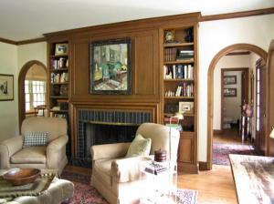 An expansive fireplace is flanked by wooden paneled shelving; the archway leads to the dining room.