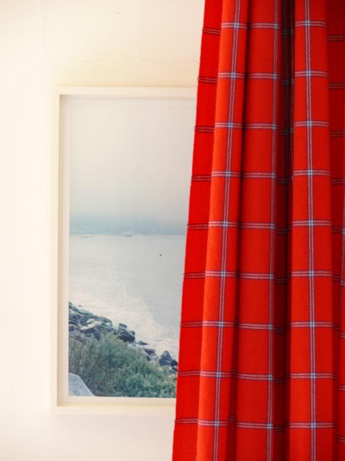 In the city, where ocean views are few and far between, a photograph of a rocky beach plays a little visual trickery peeking out from behind a curtain.