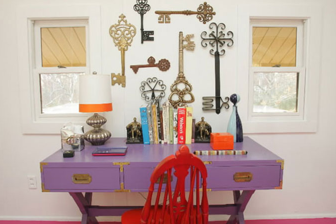 A reserved room with small windows gets a bold makeover with oversized antique keys, clashing colors, a vintage desk repainted in purple, and a fuchsia-toned floor.