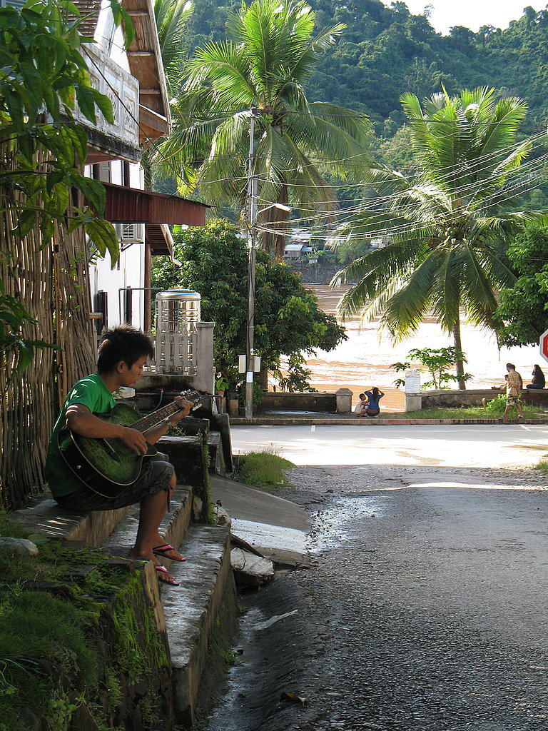 Boy Playing Guitar Near the Mekong River