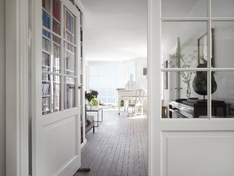 On the piano overlooking the sea is a bust of Marie Antoinette original to the house. Iron and stone furniture add warmth to the all-white room. A built-in bookcase with doors keeps a collection contained.