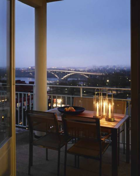 A view of Stockholm at night from the terrace, which is furnished with the Lotus Hurricane Light ($58.50) by Kristina Starck, a table by Ekerö, and chairs from Gloster.