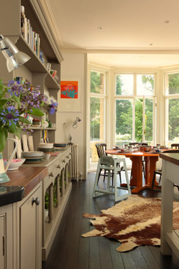 In the kitchen, a round table set in a bay window makes for a pleasant view, and a hide rug softens up the wood floors.