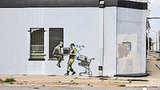 Well-known yet pseudo-anonymous British graffiti artist Banksy has stenciled often-satirical pieces of art on topics such as politics, culture, and ethics throughout the world. His work has been auctioned for thousands of dollars, and has been said to be the cause of raised property rates and gentrification in neighborhoods where he works. Shown here on a New Orleans wall is two military men looting a store for stereo equipment, where the military still remain after Hurricane Katrina (a time when looting was rampant). Source